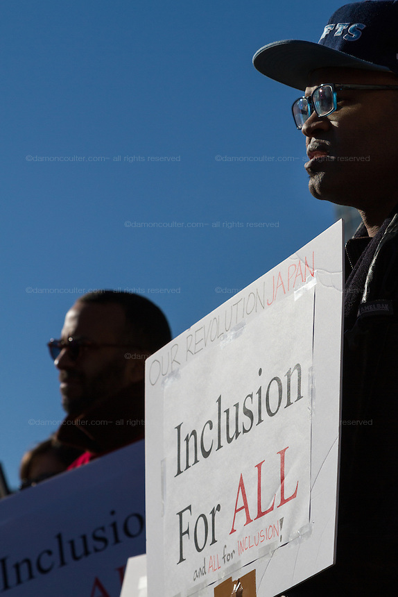 An African American man holds a signs saying Inclusion For All at a protest march and rally organised by the Alliance for an Inclusive America group against the perceived anti-Muslim and anti-foreigner immigration policies of President Donald Trump, Shibuya, Tokyo, Japan. Sunday February 12th 2017. The Alliance of an Inclusive America is a multi-faith non-partisan group. About 250 Americans, other ex-pats and japanese people took part in the march to show people around the world they reject the Executive Order President Trump enacted at the end of January, indefinitely suspending the resettlement of Syrian refugees and temporarily banning people from seven majority Muslim countries from entering the United States.