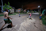 Displaced by the construction of the Belo Monte Dam from their villages along the Xingu River, indigenous children play cricket on the street at night in a housing project for displaced families in Altamira, Brazil. As many as 40,000 people were displaced by the construction of the dam and flooding of the river.  Because the area where they were resettled is outside the city and has no phone service and little transportation, many people have moved away temporarily or permanently.
