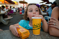 Caterina Miserandino sips some cola as she holds a hod dog at the original Nathan's Famous restaurant stands on Coney Island in New York city borough of Brooklyn, Sunday July 31, 2011. The original Nathan's restaurant stands, a company that operates a chain of U.S.-based fast food restaurants specializing in hot dogs, is located at the corner of Surf and Stillwell Avenues in Brooklyn.