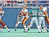 Washington Redskins quarterback Jay Schroeder (10) looks for a receiver during  the game against the Philadelphia Eagles at Veterans Stadium in Philadelphia, Pennsylvania on November 8, 1987.  Defending on the play are right linebacker Garry Cobb (50) and right defensive tackle Jerome Brown (99). Redskins left offensive tackle Joe Jacoby (66) is blocking Brown at right.  The Eagles won the game 31 - 27.<br /> Credit: Arnie Sachs / CNP