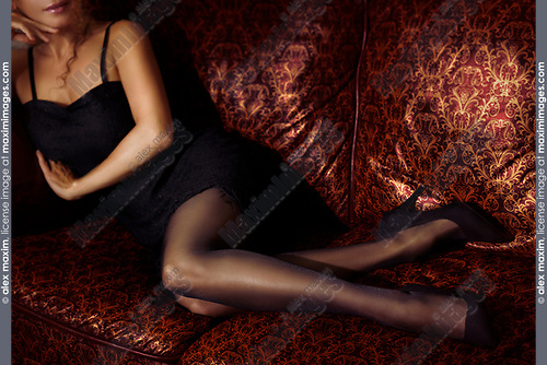 Closeup of legs of a sexy woman lying on a couch wearing a short black dress, black stockings and high heel shoes