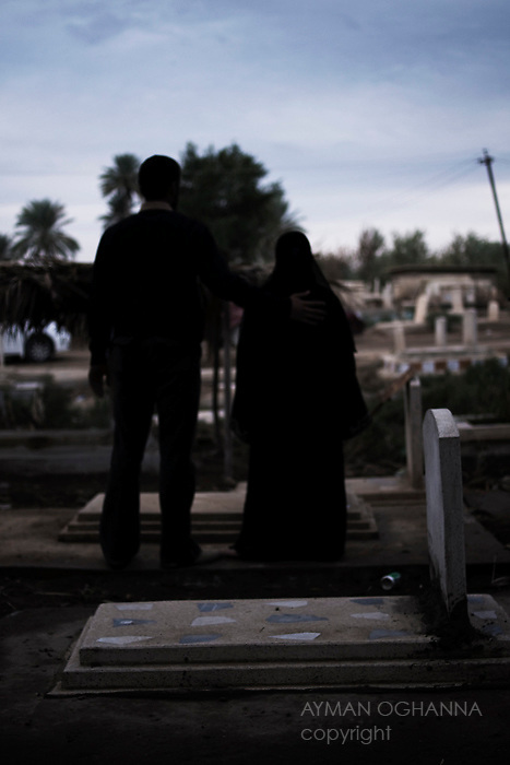 Arab Jabor Cemetery; Baghdad, Iraq  : Wed, Nov 25, 2009 :..Noor Thieb, 14, alogside her cousin Abbas Salman, 19, pays her respects at a family member's grave in a cemetery in Baghdad. Taking cover underneath a bed, Thieb watched as Sunni militants murdered her mother and three sisters. This is the first time she has visited their graves..Ayman Oghanna For The Guardian