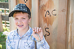 Michael Blake with his great grandfather's &quot;AC&quot; brand.<br /> <br /> The Busi family and friends use hot irons to christen and brand the new pump shed at their corrals near Jackson, California.