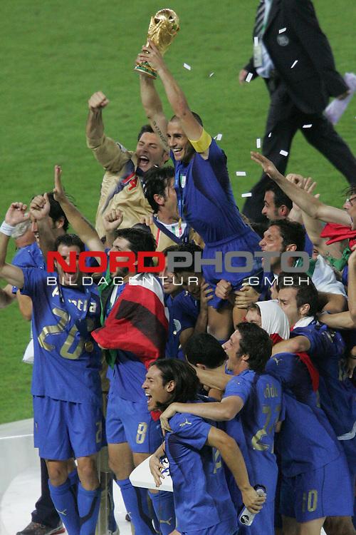 FIFA WM 2006 -  Final - Finale<br /> Play    #64  (09. Juli ) Italien - Frankreich 5:3 n. E. <br /> <br /> Fabio Cannavaro (Mitte) von Italien steht bei der Siegerehrung auf dem Podest und stemmt den Pokal in den Himmel.<br /> <br /> <br /> Foto &copy; nordphoto