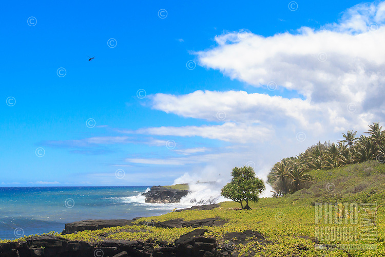 A helicopter hovers over lava entering the ocean at Fox's Landing on the Big Island.