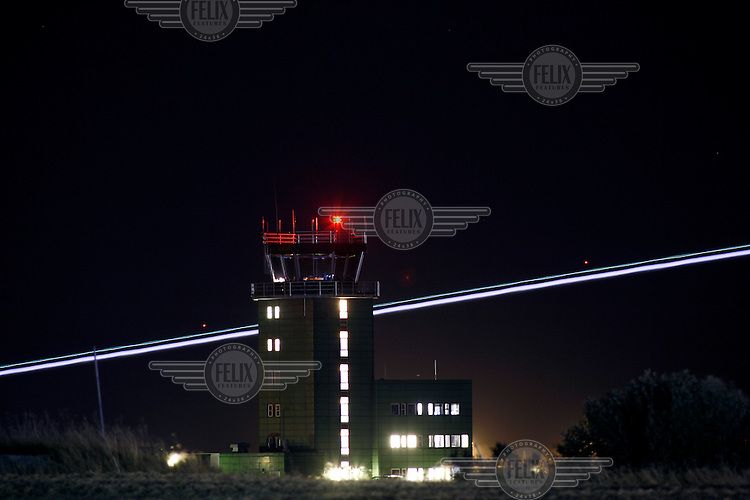 Fighter plane with afterburner leaves trail of light past the control tower. BOLD AVENGER 2007 (BAR 07), a NATO  air exercise at Ørland Main Air Station, Norway. BAR 07 involved air forces from 13 NATO member nations: Belgium, Canada, the Czech Republic, France, Germany, Greece, Norway, Poland, Romania, Spain, Turkey, the United Kingdom and the United States of America. The exercise was designed to provide training for units in tactical air operations, involving over 100 aircraft, including combat, tanker and airborne early warning aircraft and about 1,450 personnel.
