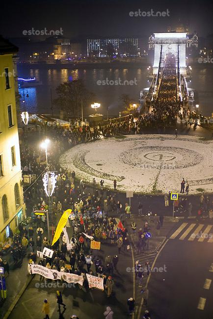 """UNGARN, 21.12.2018, Budapest V. Bezirk. Zug der Opposition zur Residenz des Staatspraesidenten János Áder, der das von der Fidesz-Regierung eingebrachte """"Sklavengesetz"""" unterzeichnet hat, das die Zahl der moeglichen Ueberstunden massiv erhoeht und ihre Abrechnung erschwert. –Ueberqueren der Kettenbruecke, einen Generalstreik fordernd. Auf dem Kreisverkehr prangt das Logo des Protests, O1G, """"Orbán ist eine Wichse"""".   March by the opposition to the residency of president Janos Ader who has signed the """"slave law"""" proposed by the Fidesz government, allowing for a massive rise in overtime work while hampering its payoff. –Crossing the Chain Bridge calling for a general strike. The roundabound carries the protest logo O1G, """"Orban is a spunk"""".  © Martin Fejer/estost.net"""