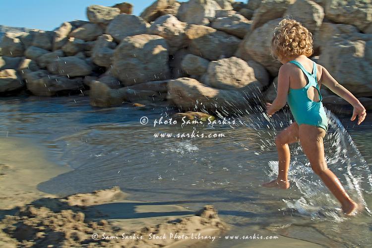 Little girl splashing in a tidal pool at the beach, Prophete, Marseille, France.