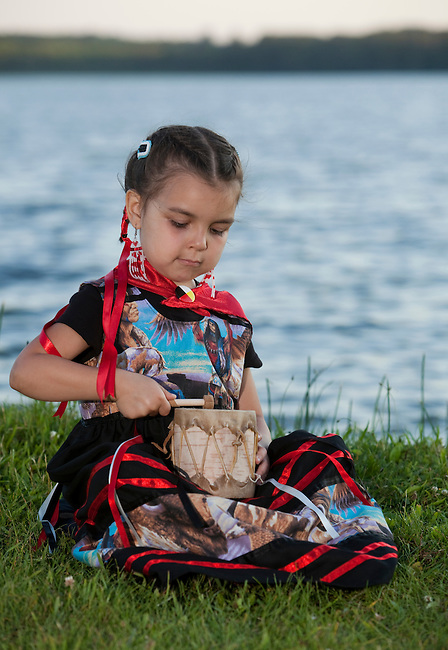 Ojibwe child uses a traditionally made birchbark tom tom drum covered with rawhide next to a lake, Midland Ontario.