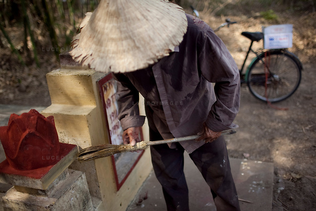 Linh, 53, paints his grandmother's grave outside of Ho Chi Minh City, Vietnam. Vietnamese restore the graves of their relatives during the Lunar New Year...Kevin German / LUCEO