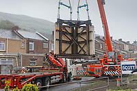 Pictured: The Banksy is hoisted by a crane onto a flat bed lorry. Wednesday 29 May 2019<br /> Re: Contractors are working to move Banksy's Season Greeting, now owned by John Brandler, which appeared on a garage wall in Port Talbot, to a new location in the same town in south Wales, UK.