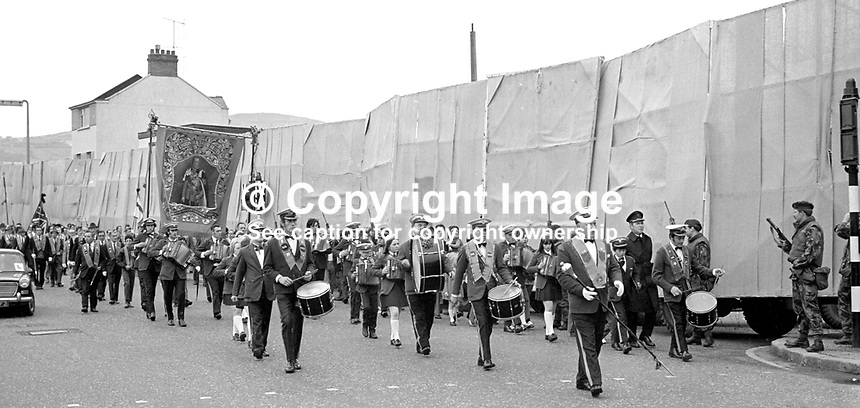 Orangemen taking part in the annual Twelfth celebration pass a Belfast, flash point where screens have been erected at a road junction to prevent clashes with parade opponents. Behind the screens are army personnel carriers. 12th July 1972. 197207120422a<br />