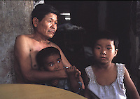 Chen Zi Huang, 58, and Qi Qi, 3, male and Gwen Gwen, 5, female eat rice and fish. The children are kept in a cage in a village house belonging to their uncle during the daytime.  The children's parents are both in prison and the uncle is too poor to afford child care for the children and are afraid they may be stolen a common problem in China....PHOTO BY SINOPIX