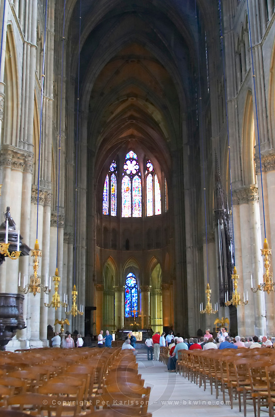 Inside the cathedral in Reims with impressive stained glass windows, chandeliers, chairs and a group of people sitting at the front, Reims, Champagne, Marne, Ardennes, France, low light grainy grain