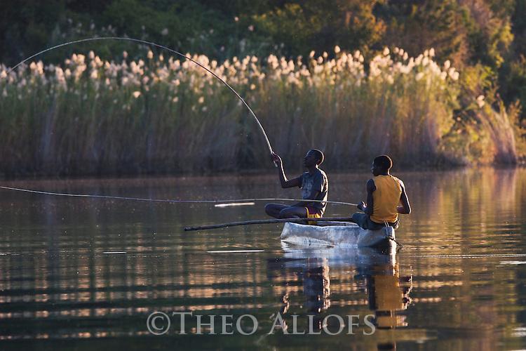 Botswana, Moremi Game Reserve, Okavango Delta, fishermen in mokoro (dugout canoe) on Okavango River