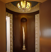 A modern sculpture is displayed in an alcove between two ornate doorways in this small circular hallway
