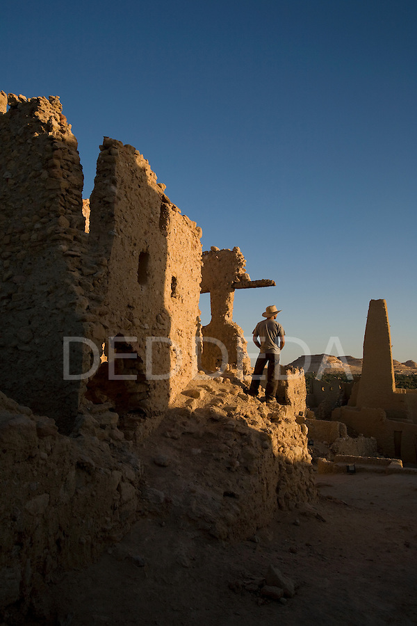 A male tourist stands within the Temple of the Oracle, dedicated to Amun, and was built in the 6th century BC. The Temple is one of the most revered oracles in the ancient Mediterranean, and it sits in the ruins of Aghurmi village in the Siwa Oasis, Egypt. Alexander the Great consulted the priests of Amun at the Temple of the Oracle in 331 BC.
