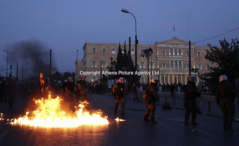 Pictured: A firebomb explodes near riot police in front of the Greek Parliament Sunday 09 May 2016<br /> Re: Riots break out between protesters and police in Syntagma Square, while MPs in the Greek Parliament vote for new tax, pension and welfare reforms in Athens, Greece