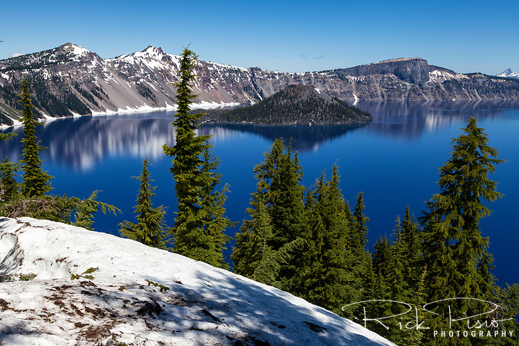 Wizard Island and Crater Lake with late June snow still on the ground.
