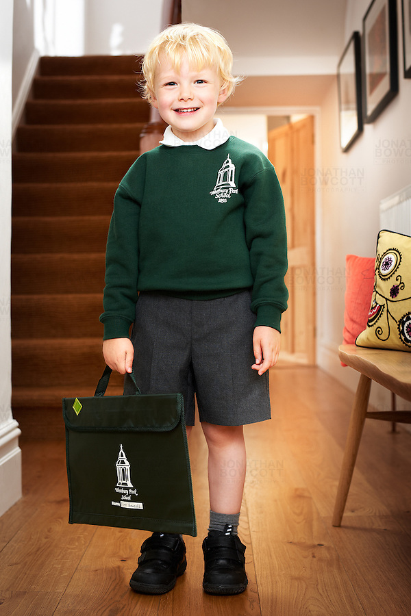 A 4 year old boy prepares to leave the house for his first day at Westbury Park Primary school, Bristol UK.