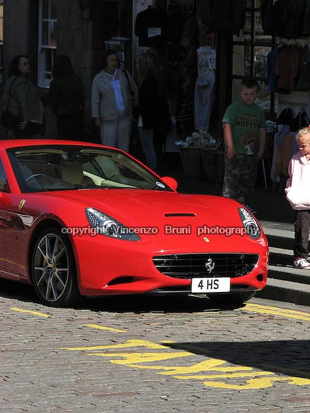 A Ferrari California in Rosso Scuderia red livery being admired by a very young Ferrari fan.