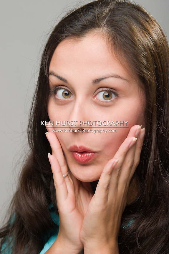 Beautiful young brunette woman with facial expression of surprise.