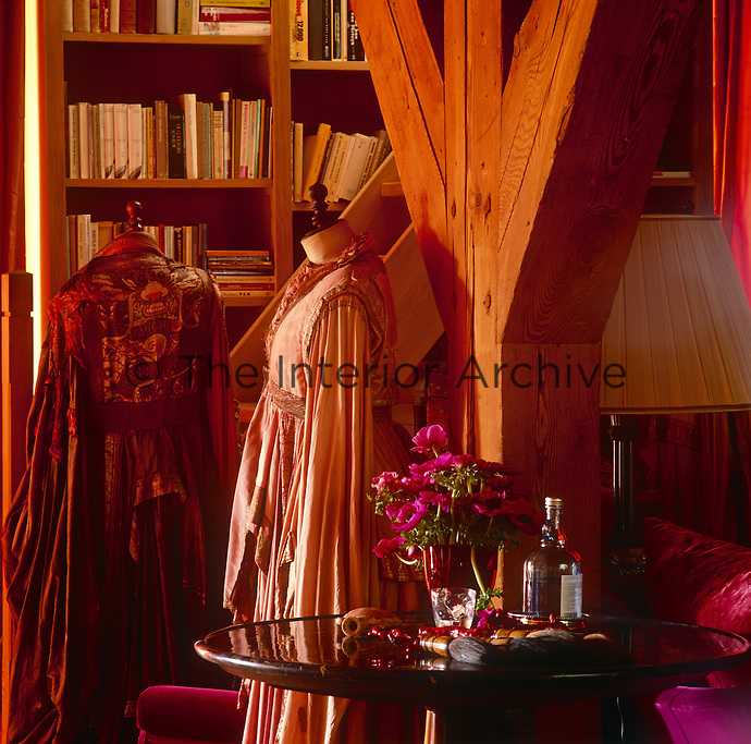 Two tailor's dummies are draped in dresses and stand in front of wooden shelves filled with books. A flower arrangement and paint brushes are placed on a mirror topped table.