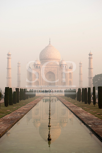 Agra, Uttar Pradesh, India. The Taj Mahal seen from the end of the al Hawd al-Kawthar tank, with its reflection, in the early morning mist.