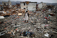 Ichiko Hirayama stands behind bottles with drinks retrieved from rubbles of her home in the destroyed residential part of Ofunato more than a week after the area was devastated by a magnitude 9.0 earthquake and tsunami March 20, 2011.   REUTERS/Damir Sagolj (JAPAN)