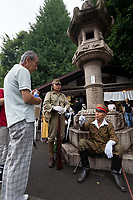 An older Japanese man in Imperial Army uniform talks with another man as Yasukuni shrine marks the 72nd anniversary of the end of the Pacific War. Yasukuni Shrine, Kudanshita, Tokyo Japan. Tuesday August 15th 2017. Nominally a event to honour Japan's war dead and call for continued peace, this annual gathering  at Tokyo's controversial Yasukuni  Shine also allows many Japanese nationalists to display their nostalgia for their Imperial past.Rightwing paramilitary groups, Imperial cos-players, politicians and many ordinary citizens come together at the shrine to march and wave flags. The day goes almost unreported in the mainstream Japanese media.