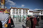 Chinese troops marching in front of Tibets holiest temple, the Jokhang. Thousands of pilgrims cirkle the temple, a Kora.