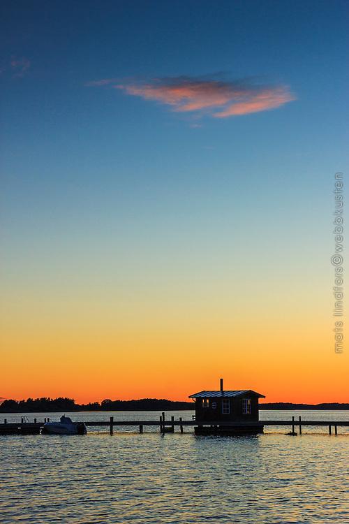 Sjöbod på brygga i solnedgång vid havet nära Torö Nynäshamn