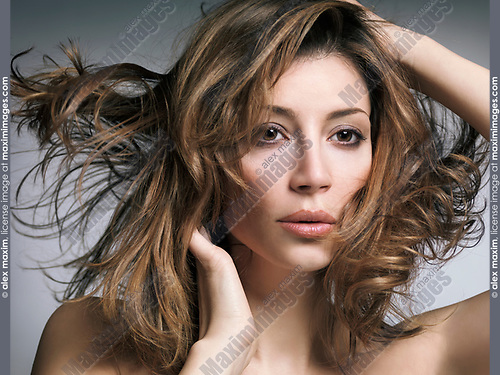 Beauty portrait of a young caucasian woman with flying light brown hair and natural makeup on gray background