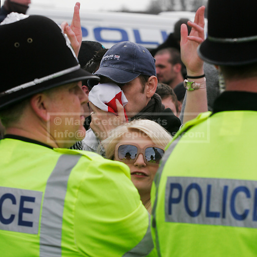 A sunglasses wearing female EDL supporter stares over the shoulders of two policemen as a male protester covers his face.