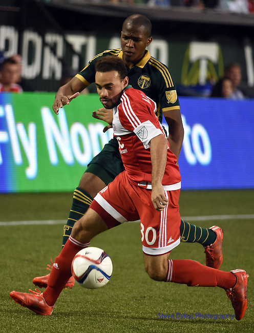 Jun 6, 2015; Portland, OR, USA; New England Revolution defender Kevin Alston (30) and Portland Timbers forward/midfielder Darlington Nagbe (6) battle for a ball during the second half of the game at Providence Park. The Timbers won the game 2-0. Mandatory Credit: Steve Dykes-USA TODAY Sports