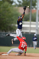 Milwaukee Brewers second baseman Franly Mallen (10) jumps for a throw as Luis Gonzalez (59) slides in during an Instructional League game against the Cincinnati Reds on October 6, 2014 at Maryvale Baseball Park Training Complex in Phoenix, Arizona.  (Mike Janes/Four Seam Images)