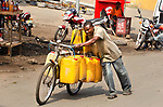 Pictured: Jerry cans filled with petrol loaded on a bike, having purchased the fuel to be sold on to scooter riders in Goma, Congo.<br /> <br /> Goods as varied as mattresses and cabbages are precariously balanced on bikes and hauled enormous distances to be sold at market stalls.  A series of photos show workers in the Democratic Republic of Congo and neighbouring Rwanda walking up to 20 miles as they transport their wares from small villages and farms to city marketplaces.<br /> <br /> One shot even shows a man riding a motorbike with seven multi-coloured mattresses tied to the back.  Bicycles laden with sacks bursting full of potatoes will weight more than 30 stones, as workers wheel them from their homes to be sold.  SEE OUR COPY FOR DETAILS.<br /> <br /> <br /> Please byline: Joe Dordo Brnobic/Solent News<br /> <br /> © Joe Dordo Brnobic/Solent News & Photo Agency<br /> UK +44 (0) 2380 458800