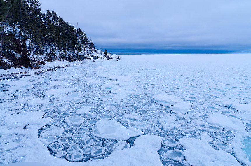 Ice chunks along the Lake Superior shoreline creating the effect of puzzle pieces on a cold spring day. Marquette, MI