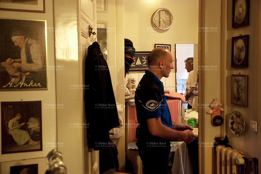 "Switzerland. Geneva. Paquis neighborhood. A police officer talks to a man suspected of domestic violence aginst his wife. Drawings from Albert Samuel Anker on the wall. Albert Samuel Anker (1831-1910) was a Swiss painter and illustrator who has been called the ""national painter"" of Switzerland because of his enduringly popular depictions of 19th-century Swiss village life. Domestic violence, also known as domestic abuse, spousal abuse, battering, family violence, and intimate partner violence (IPV), is defined as a pattern of abusive behaviors by one partner against another in an intimate relationship such as marriage. Domestic violence, so defined, has many forms, including physical aggression or assault. 29.06.12 © 2012 Didier Ruef"