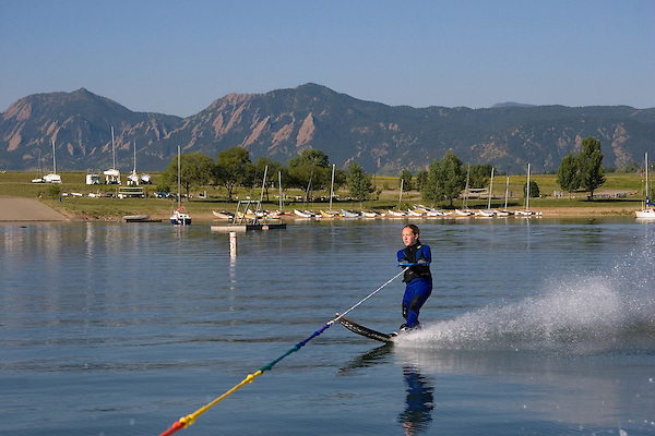 Female slalom waterskier at Boulder Reservoir with Flatirons rock formation behind, Boulder, Colorado, USA .  John leads private photo tours in Boulder and throughout Colorado. Year-round. .  John offers private photo tours in Denver, Boulder and throughout Colorado. Year-round.