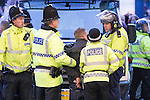© Joel Goodman - 07973 332324 . 13/05/2013 . Manchester , UK . Police detain a man in handcuffs at the foot of Market Street after police and fans scuffled when police attempted to push Manchester United fans up Market Street , away from the City Store . Police confront 100s of Manchester United fans outside the Manchester City store on Market Street after the Manchester United victory parade , this evening (13th May 2013) Photo credit : Joel Goodman