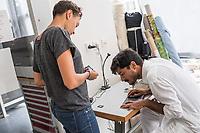 """Das Berliner Start-up """"mimycri"""" produziert Taschen aus den Gummiplanen gestrandeter Fluechtlingsboote.<br /> Statt Griechenlands Straende im Muell der gestrandeten Fluechtlingsboote ersticken zu lassen, stellt das Berliner Unternehmen """"mimycri"""" daraus Taschen und Rucksaecke her und bietet Fluechtlingen eine Chance auf Normalitaet und Regelmaessigkeit.<br /> Im Bild vlnr.: Nora Azzaoui, 30-Jaehrige Unternehmensberaterin aus Berlin und Abid Ali, gefluechteter Schneider aus Pakistan besprechen den Schnitt einer Tasche.<br /> 8.8.2017, Berlin<br /> Copyright: Christian-Ditsch.de<br /> [Inhaltsveraendernde Manipulation des Fotos nur nach ausdruecklicher Genehmigung des Fotografen. Vereinbarungen ueber Abtretung von Persoenlichkeitsrechten/Model Release der abgebildeten Person/Personen liegen nicht vor. NO MODEL RELEASE! Nur fuer Redaktionelle Zwecke. Don't publish without copyright Christian-Ditsch.de, Veroeffentlichung nur mit Fotografennennung, sowie gegen Honorar, MwSt. und Beleg. Konto: I N G - D i B a, IBAN DE58500105175400192269, BIC INGDDEFFXXX, Kontakt: post@christian-ditsch.de<br /> Bei der Bearbeitung der Dateiinformationen darf die Urheberkennzeichnung in den EXIF- und  IPTC-Daten nicht entfernt werden, diese sind in digitalen Medien nach §95c UrhG rechtlich geschuetzt. Der Urhebervermerk wird gemaess §13 UrhG verlangt.]"""