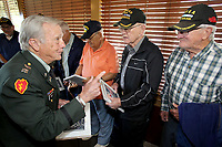 NWA Democrat-Gazette/DAVID GOTTSCHALK   Captain Clifford Mosier (from left), retired Army, hands out a book titled Korea Reborn A Grateful Nation Monday, May 1, 2017, to Alfaro Marinez, Max Page and Lehman Turner, all Korean War veterans, in Fayetteville. The three were part of a group of nine Korean War veterans that were recognized by the Northwest Arkansas Chapter of Military Officers Association of America Monday and received the book. The books were published by the South Korean government in gratitude of the United States military service in the war and documents the growth and progress that country has sustained over the past 60 years.