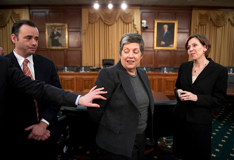 WASHINGTON, DC - March 02: An aide gets Homeland Security Secretary Janet Napolitano's attention as she and other aides wait for the start of the House Appropriations Subcommittee on Homeland Security hearing on the administrations' fiscal 2012 budget request. The House was conducting a series of votes, which delayed committee members' arrival. (Photo by Scott J. Ferrell/Congressional Quarterly)
