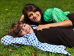 Portrait of two happy smiling children, sister and younger brother, lying down on green grass.