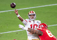 2nd February 2020, Miami Gardens, Florida, USA;  San Francisco 49ers Quarterback Jimmy Garoppolo (10) throws the ball and then is hit by Kansas City Chiefs Defensive Tackle Mike Pennel (64) resulting in an interception by Kansas City Chiefs Cornerback Bashaud Breeland (not shown) during the NFL Super Bowl LIV  game between the Kansas City Chiefs and the San Francisco 49ers at the Hard Rock Stadium in Miami Gardens