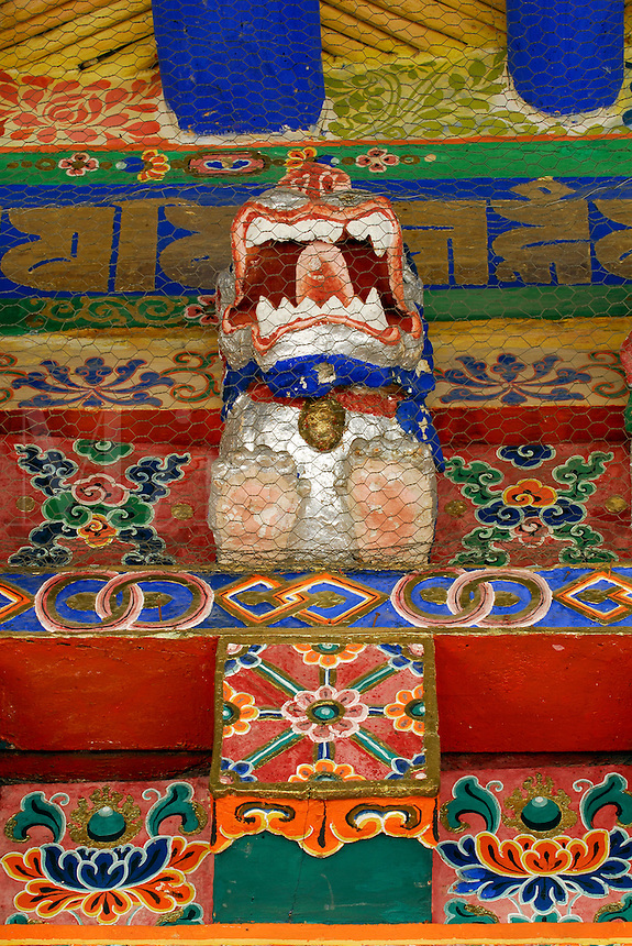 Wood-carved and painted, animal protector deity guards the monastery doorway to prevent entry of evil spirits, Drepung Monastery, Lhasa, Tibet, China..