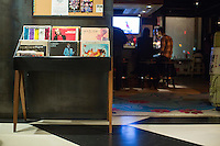 "A collection of vinyl records stands on display in the lobby of The Verb Hotel in the Fenway neighborhood of Boston, Massachusetts, USA, on Friday, Dec. 4, 2015. The hotel is considered a ""boutique hotel"" and has collections on display throughout the premises of music memorabilia from the Boston area. The lobby has a record player available to play from this collection. At right, patrons sit at the bar at Hojoko, a Japanese bar and restaurant in The Verb Hotel."