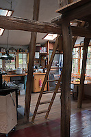 A rustic ladder leading up to the sleeping area divides the kitchen from the living room