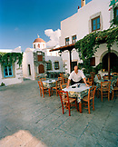 GREECE, Patmos, Chora, Dodecanese Island, a man sets tables at a restaurant in the island top village of Chora
